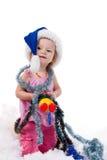 Bebé en el sombrero de Santa en oropel y nieve artificial Imagen de archivo libre de regalías