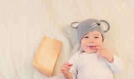 Bebé en el sombrero del ratón que miente en la manta con queso Fotografía de archivo