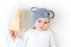 Bebé en el sombrero del ratón que miente en la manta con queso Foto de archivo libre de regalías