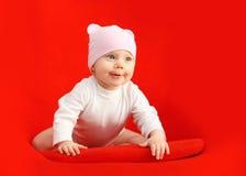 Bebé en el sombrero que se sienta y que juega en la butaca roja Fotos de archivo libres de regalías