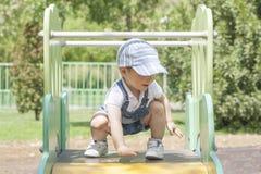 Bebé en el top del resbalador Concepto del balance Fotografía de archivo libre de regalías
