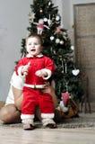 Bebé en el traje de Papá Noel que se coloca con la madre en el adornamiento del árbol de navidad Fotografía de archivo libre de regalías