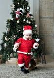 Bebé en el traje de Papá Noel que se coloca en el adornamiento del árbol de navidad Imágenes de archivo libres de regalías