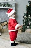 Bebé en el traje de Papá Noel que se coloca en el adornamiento del árbol de navidad Foto de archivo