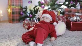 Bebé en el traje de Papá Noel que se sienta bajo el árbol de navidad y caídas almacen de metraje de vídeo