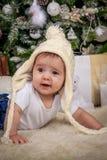 Bebé en el traje del duende que juega con el tren de madera viejo y los osos suaves del juguete debajo del árbol de navidad, vint imágenes de archivo libres de regalías