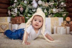 Bebé en el traje del duende que juega con el tren de madera viejo y los osos suaves del juguete debajo del árbol de navidad, vint fotografía de archivo