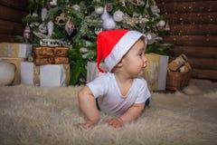 Bebé en el traje del duende que juega con el tren de madera viejo y los osos suaves del juguete debajo del árbol de navidad, vint imagen de archivo libre de regalías