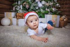 Bebé en el traje del duende que juega con el tren de madera viejo y los osos suaves del juguete debajo del árbol de navidad, vint foto de archivo libre de regalías