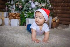 Bebé en el traje del duende que juega con el tren de madera viejo y los osos suaves del juguete debajo del árbol de navidad, vint fotos de archivo libres de regalías