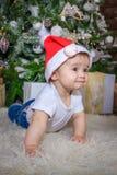 Bebé en el traje del duende que juega con el tren de madera viejo y los osos suaves del juguete debajo del árbol de navidad, vint fotos de archivo