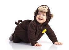 Bebé en el traje del mono que mira para arriba sobre blanco Fotografía de archivo libre de regalías
