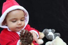 Bebé en el traje que juega, fondo negro de Papá Noel Fotos de archivo libres de regalías