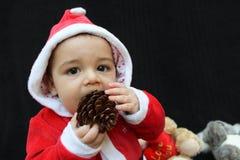 Bebé en el traje que juega, fondo negro de Papá Noel Foto de archivo