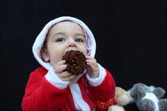 Bebé en el traje que juega, fondo negro de Papá Noel Imagen de archivo libre de regalías