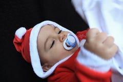 Bebé en el traje que juega, fondo negro de Papá Noel Imagenes de archivo