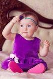 Bebé en el vestido violeta que toca su venda y que mira a la izquierda Imagen de archivo