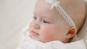 Bebé en el vestido y la venda blancos metrajes