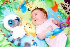 Bebé en estera educativa foto de archivo