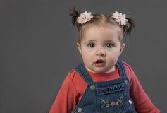 Bebé en guardapolvos de la mezclilla en fondo gris imágenes de archivo libres de regalías