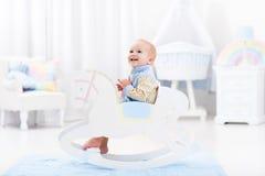 Bebé en juguete del caballo mecedora Foto de archivo libre de regalías