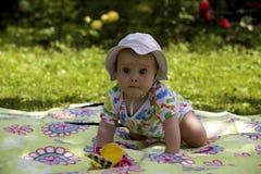 Bebé en la alfombra de la comida campestre en hierba Imágenes de archivo libres de regalías