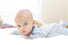 Bebé en la cama, arrastrándose Fotografía de archivo