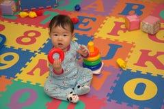 Bebé en la estera del alfabeto Fotos de archivo libres de regalías