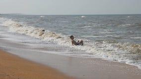 Bebé en la playa, en la onda marítima Dos muchachos en la arena de oro que juega en la resaca la onda con la cabeza cubre metrajes