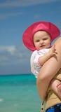 Bebé en la playa que es sostenida Fotografía de archivo