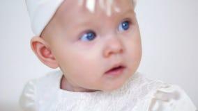 Bebé en la sentada blanca del vestido y de la venda almacen de metraje de vídeo
