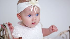 Bebé en la sentada blanca del vestido y de la venda almacen de video