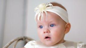 Bebé en la sentada blanca del vestido y de la venda metrajes