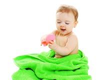 Bebé en la toalla que juega con el juguete de goma Imagenes de archivo
