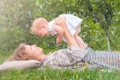 Bebé en las manos del ` s de la madre Niño sonriente con la madre Concepto del principio de la vida Señora del negocio con un niñ fotos de archivo