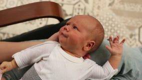 Bebé en las rodillas del mes, miradas recién nacidas en el mundo almacen de video