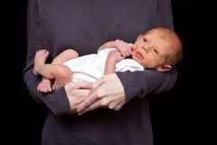 Bebé en los brazos de la madre Fotos de archivo
