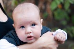Bebé en madre \ 'brazos de s Imagen de archivo libre de regalías