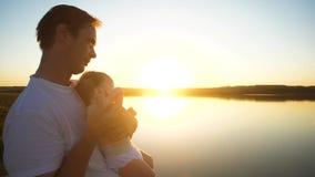 Bebé en manos del papa en la puesta del sol del sol ardiente Cámara lenta metrajes