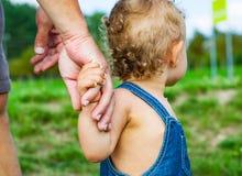 Bebé en parque Confíe en las manos de la familia del hijo y del padre del niño imagenes de archivo