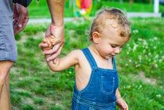 Bebé en parque Confíe en las manos de la familia del hijo y del padre del niño fotografía de archivo