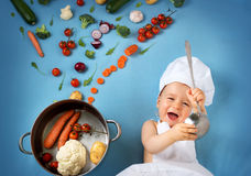 Bebé en sombrero del cocinero con cocinar la cacerola y verduras Fotografía de archivo