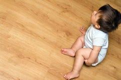 Bebé en suelo de madera imagenes de archivo