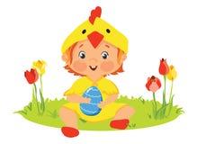 Bebé en traje del polluelo con el huevo decorativo Imagenes de archivo