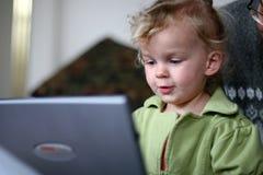 Bebé en un ordenador Imagenes de archivo