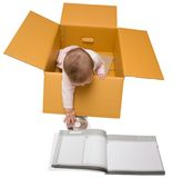 Bebé en un rectángulo con el manual y el disco de la instrucción Imágenes de archivo libres de regalías