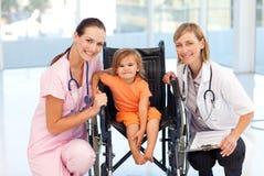 Bebé en un sillón de ruedas con la enfermera y el doctor Imágenes de archivo libres de regalías