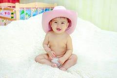 Bebé en un sombrero de vaquero rosado que se sienta en pañales en el sofá Fotos de archivo