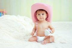 Bebé en un sombrero de vaquero rosado que se sienta en pañales en el sofá Fotos de archivo libres de regalías