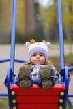 Bebé en un sombrero divertido que balancea en el patio del invierno, punto de vista de la perspectiva imagen de archivo